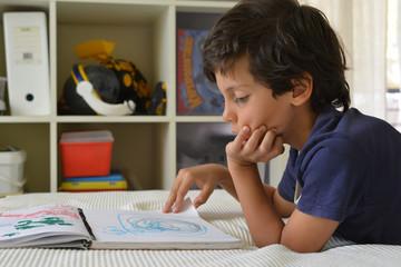 Boy watching his own artwork