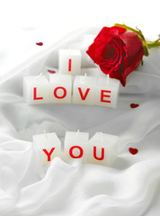 Candles with printed sign I LOVE YOU,on white fabric background