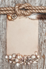 Ship rope, shells, sheet of paper, feather and wood background