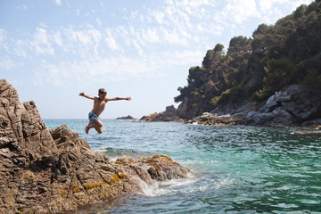 Young boy jumping into the sea