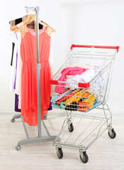 Shopping cart with clothing, on gray wall background