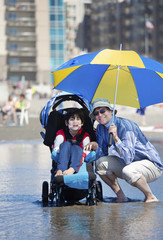 Father at beach with disabled son in wheelchair
