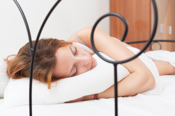 Red-haired woman sleeping on white pillow in bed