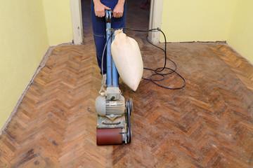 Obraz Worker polishing parquet floor with grinding machine - fototapety do salonu