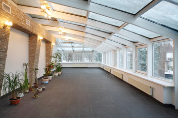 Empty conservatory with small number of plants and glass ceiling