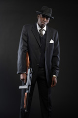 Retro african american mafia man wearing striped suit and tie an