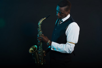 Wall Mural - Retro african american jazz musician holding his saxophone. Wear