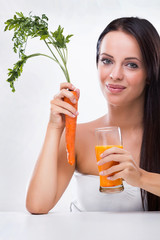 Young woman holding carrot and carrot juice