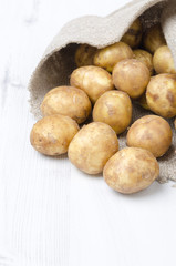 new potatoes in a sack on a white wooden board, vertical