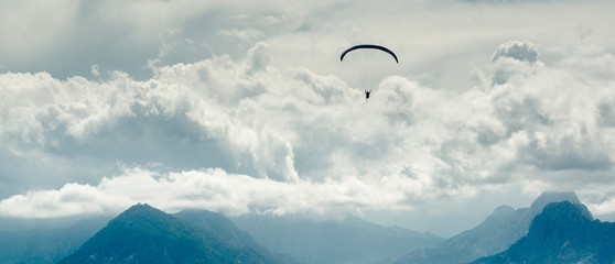 Fotobehang Luchtsport Paraglider over mountains and cloudy sky background
