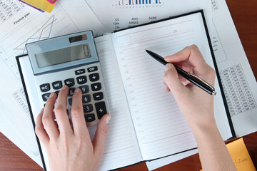 Woman hands counting on calculator on worktable background
