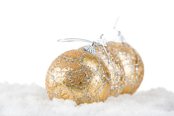 golden christmas balls on snow, selective focus