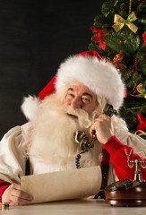 Santa Claus calling with vintage phone while reading an old roll