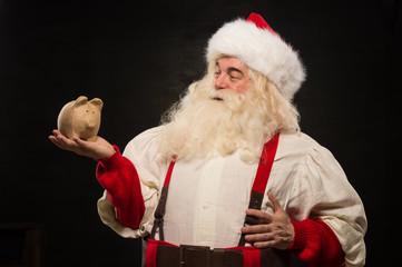 Santa Claus holding piggy bank moneybox