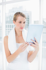 Concentrated sporty woman holding tablet pc