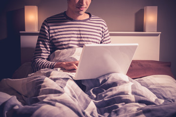 Young man sitting in bed video chatting