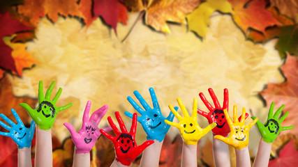 angemalte Kinderhände vor Laub-Hintergrund