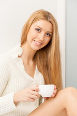 Woman with cup. Beautiful young woman drinking coffee near the w