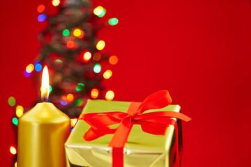 Weihnachten mit Kerze und Geschenk vor rotem Hintergrund