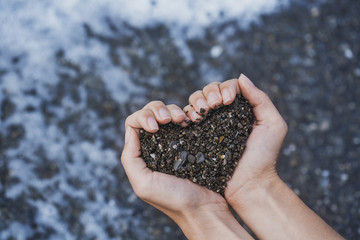 hands in the form of heart on the pebbles background