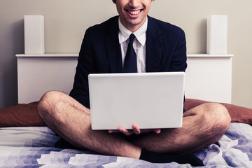 Young businessman with laptop sitting on bed in his underwear