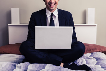 Happy young businessman sitting in bed with laptop