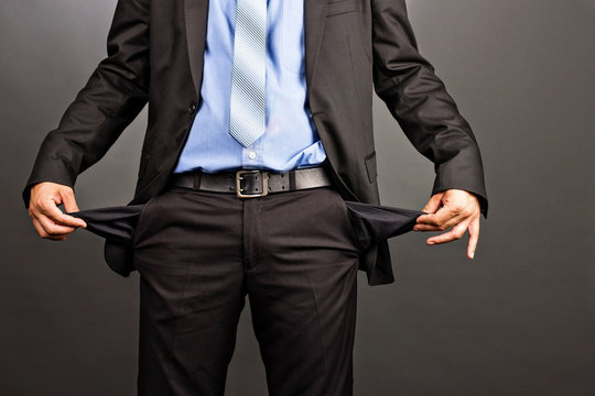 Business man showing his empty pockets