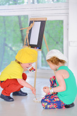 Boy and girl with watercolors sit on the floor