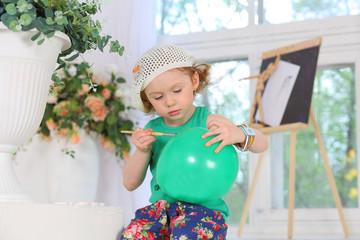The little painter paints pictures on a green balloon