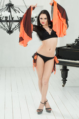 Beautiful go-go dancer in costume in a room with a piano