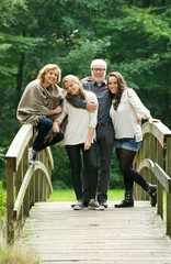 Happy family standing together on a bridge in the forest