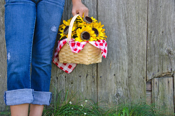 girl in jeans with sunflower basket