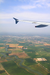 Aerial shot of a landscape from airplane with wing visible