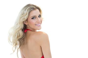 Smiling blonde model wearing red bikini looking over shoulder at
