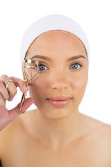 Attractive woman with headband using eyelash curler