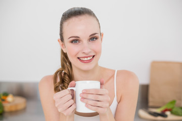 Cheerful young woman holding mug