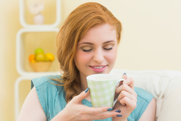 Happy redhead sitting on the couch smelling coffee