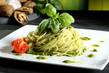 pasta spaghetti con pesto tavolo grigio sfondo verde