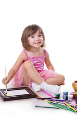 Smiling three year girl drawing with paint