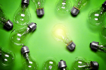 Idea concept with light bulbs on green background.