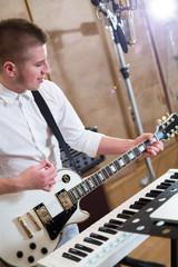 Guitarist playing guitar next to keyboards in studio