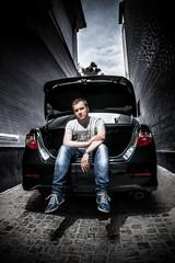 Handsome man sitting in car trunk