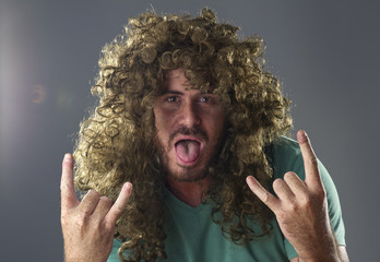 Portrait of a guy with a wig doing a rock and roll symbol