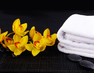 spa setting with yellow orchid with black stone with towel