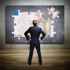 Geschäftsmann steht vor Euro-Puzzle
