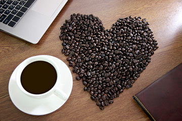 Coffee beans arranged shaped into a heart near white coffee cup.