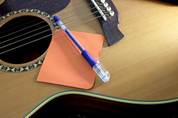 Notebook orange paper and pen on the guitar.
