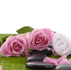 pink rose and towel with zen stones on green mat
