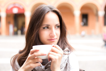 Beautiful young girl drinking a cup of coffee on a summer day