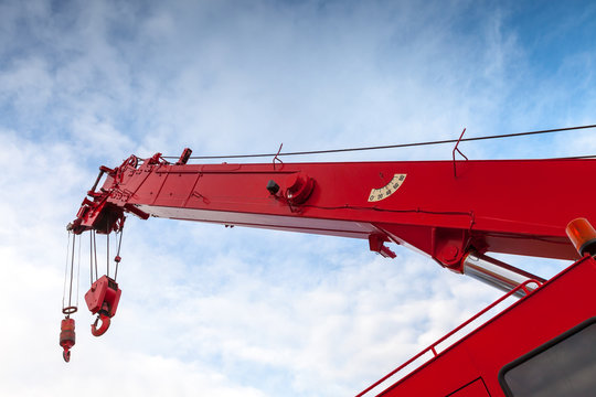 Red truck crane boom with hooks and scale weight